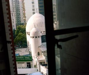Yan taraftaki apartmanın camından görünen cami manzarası.
